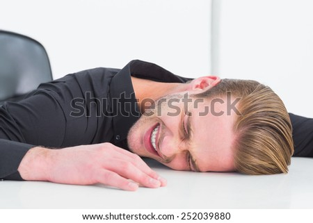 Stressed businessman banging his head on white background - stock photo