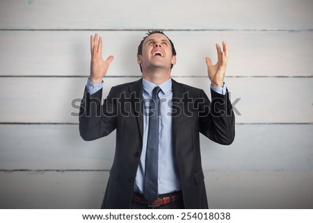 Stressed businessman gesturing against painted blue wooden planks - stock photo