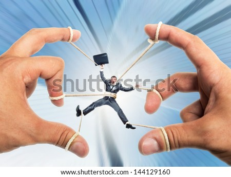 Stressed businessman governed by puppeteer hands - stock photo