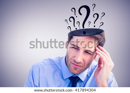 Stressed businessman holding his head against grey vignette - stock photo