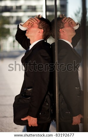Stressed businessman leaning on an office building