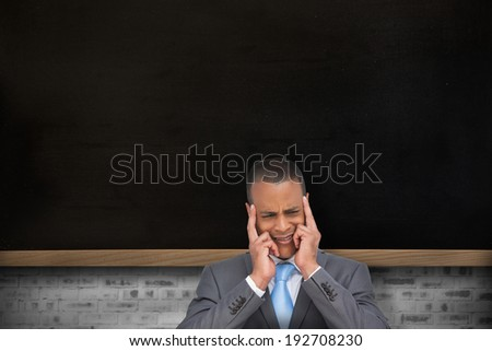 Stressed businessman putting his fingers on his temples against chalkboard on grey brick wall - stock photo