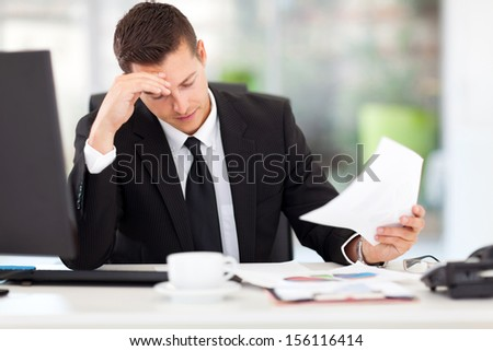 stressed businessman reading documents in office - stock photo