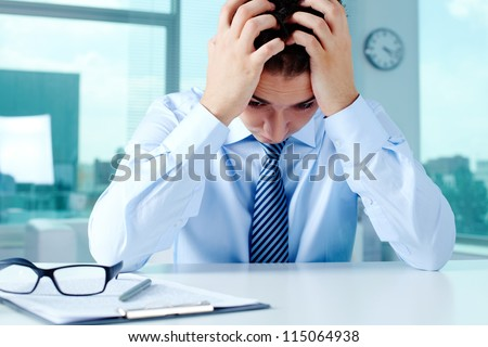 Stressed businessman sitting at workplace and touching his head - stock photo