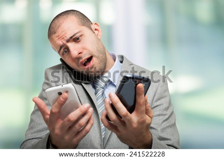Stressed businessman talking on many phones at once - stock photo