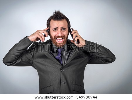 Stressed businessman talking on two phones at the same time. Business concept