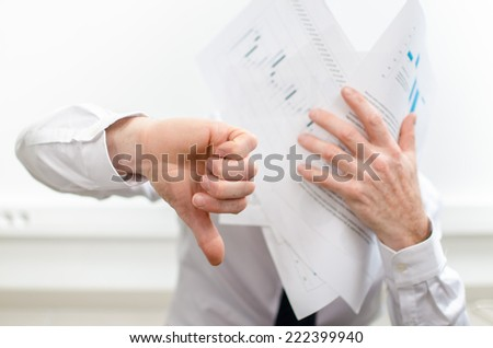 Stressed businessman, thumb down, holding bad graphs against his face - stock photo