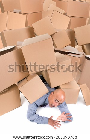 Stressed businessman under a pile of cardboard boxes - stock photo