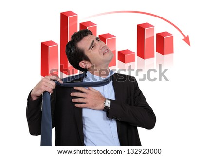 Stressed businessman with a downturn graph - stock photo