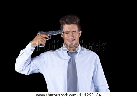 Stressed businessman with a gun pointing to his head - stock photo