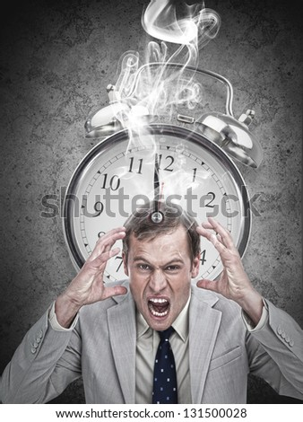 Stressed businessman with a hot deadline on grey background