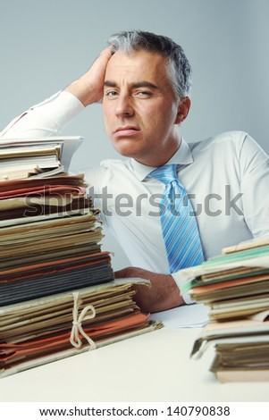 Stressed businessman, with a too much paperwork and files piled up on the table