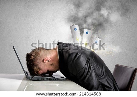 Stressed businessman with explosion of discharged battery - stock photo