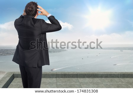 Stressed businessman with hands on head against coastline city - stock photo
