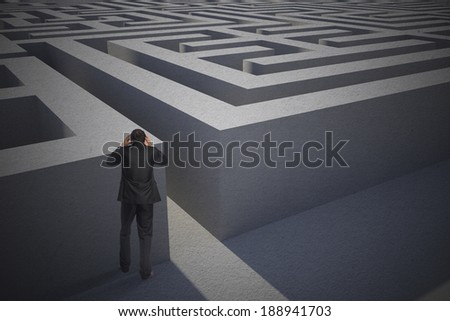 Stressed businessman with hands on head against entrance to difficult maze puzzle