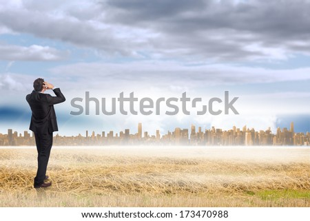 Stressed businessman with hands on head against large city on the horizon