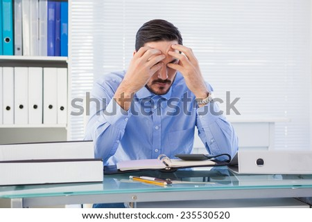Stressed businessman with hands on his head in the office - stock photo