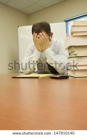 Stressed businessman with head in hands sitting by pile of books at office desk - stock photo