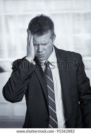 Stressed businessman with headache pain in office - stock photo