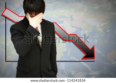Stressed businessman with low financial graph of global business - stock photo