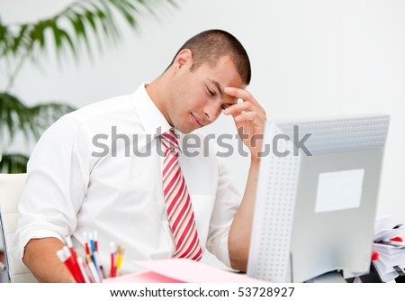 Stressed businessman working at a computer in the office - stock photo