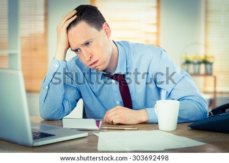 Stressed businessman working at his desk in his office - stock photo