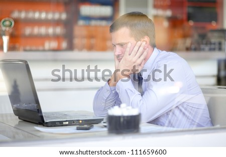Stressed businessman working in a cafe - stock photo