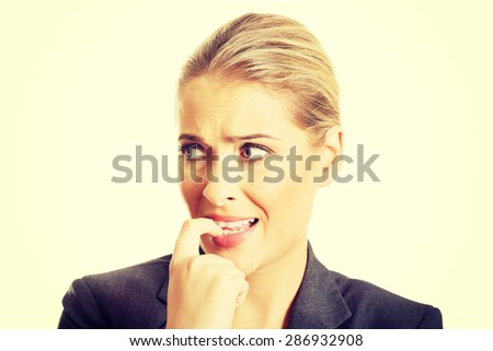 Stressed businesswoman biting her nails. - stock photo