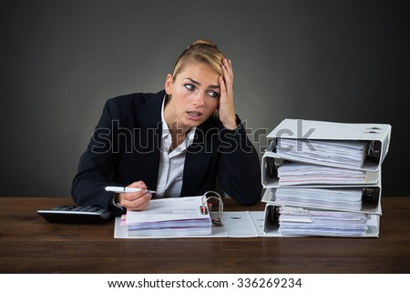 Stressed businesswoman looking at folders while working at desk over gray background - stock photo