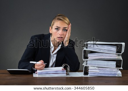 Stressed businesswoman looking at folders while working at desk over gray background
