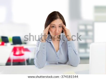 stressed businesswoman sitting at the office with hands on head