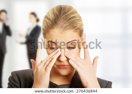 Stressed businesswoman suffering from eyes pain. - stock photo