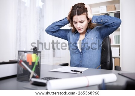 Stressed businesswoman under pressure sitting holding her head with her hands with an anguished expression as she eyes unfinished paperwork on her desk - stock photo