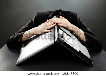 Stressed businesswoman with her laptop on her head in closeup pose, on grey background - stock photo