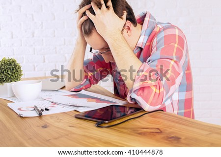 Stressed caucasian male with head in hands over wooden desk with tablet, business charts and coffee mug on white brick wall background - stock photo