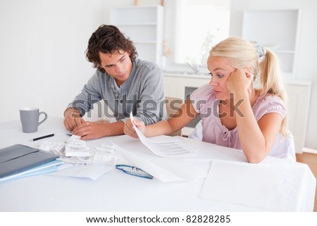 Stressed couple doing accounts in their living room