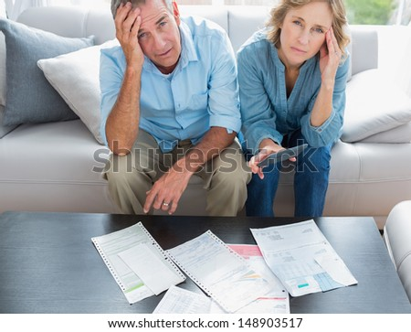 Stressed couple sitting on their couch paying their bills smiling at camera at home in the living room