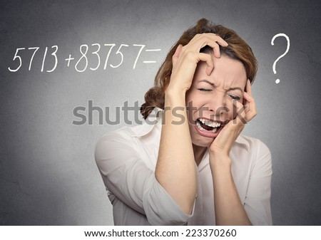 Stressed crying woman can't solve math problem on her mind isolated on grey wall background. Human face expressions, emotions, feelings - stock photo