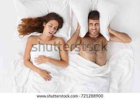 Stressed darn haired bearded man blocking ears with pillow, having annoyed expression because of his snoring wife who is sleeping in bed next to him. Snore, insomnia and sleep disorder concept