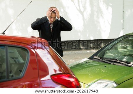 Stressed Driver Standing At Roadside After Traffic Accident - stock photo