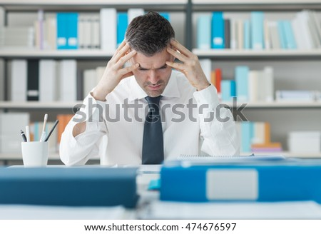 Stressed exhausted man working at office desk with head in hands, he is overloaded with paperwork, stressful job concept
