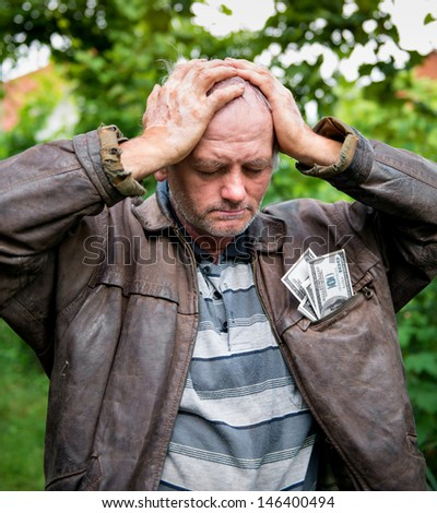 Stressed farmer with money in his jacket on natural background - stock photo