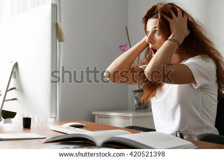 Stressed female freelancer screaming in shock, having serious computer problem. Horrified student girl clutching her head in panic, missing graduation project deadline, sitting in front of the laptop  - stock photo