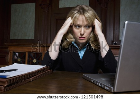Stressed female lawyer looking at laptop - stock photo