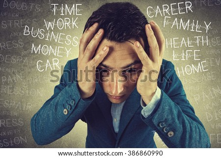 Stressed,frustrated,depressed portrait of a young student, man, holding his hands up on head isolated on grey background.Facial expression - stock photo
