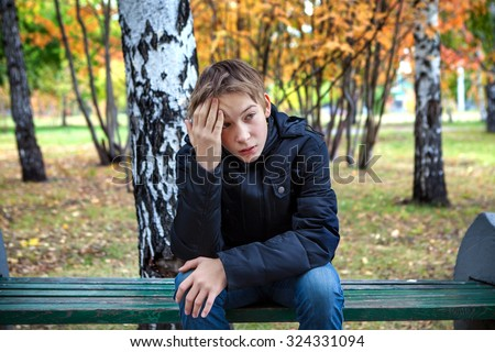 Stressed Kid sit on the Bench in the Autumn Park - stock photo