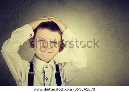 Stressed little boy having problems.Confused little boy with hand on his had over grey background.Stressed little boy having problems. - stock photo