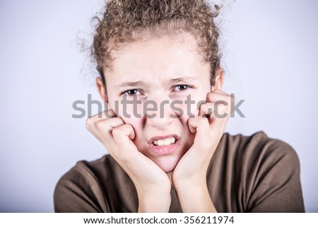 Stressed little girl having problems.Portrait of little girl suffering from headache and holding hands on her head - stock photo
