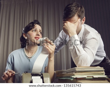 Stressed man and woman looking at their bills in the living-room at home