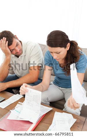 Stressed man and woman looking at their bills in the living room at home